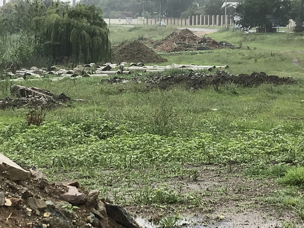 Photo of the abandoned Modderfontein Outfall Sewer construction site with concrete slabs, rubble and discarded pipes